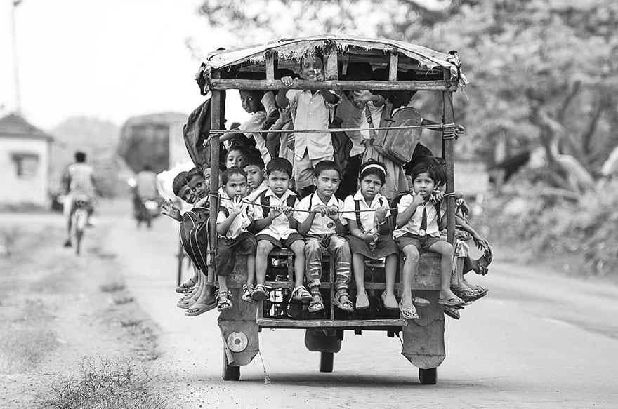 トゥクトゥクに乗って学校に向かう子供たち。インド
