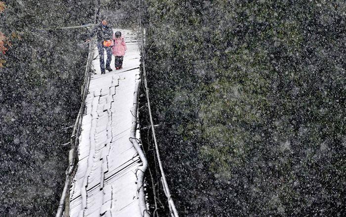 雪の中壊れた橋を渡る。中国・四川省