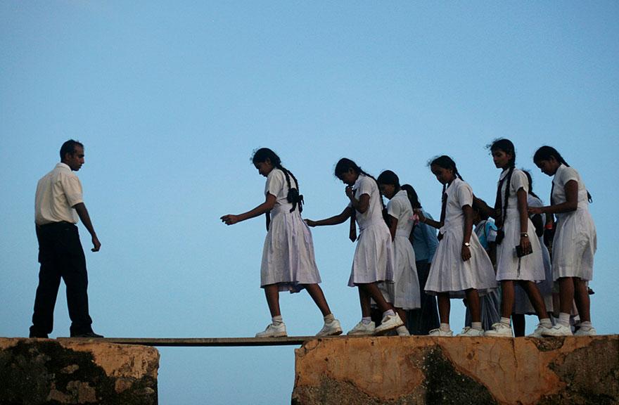 ゴールフォートの壁の上の板を歩く女子高生。スリランカ