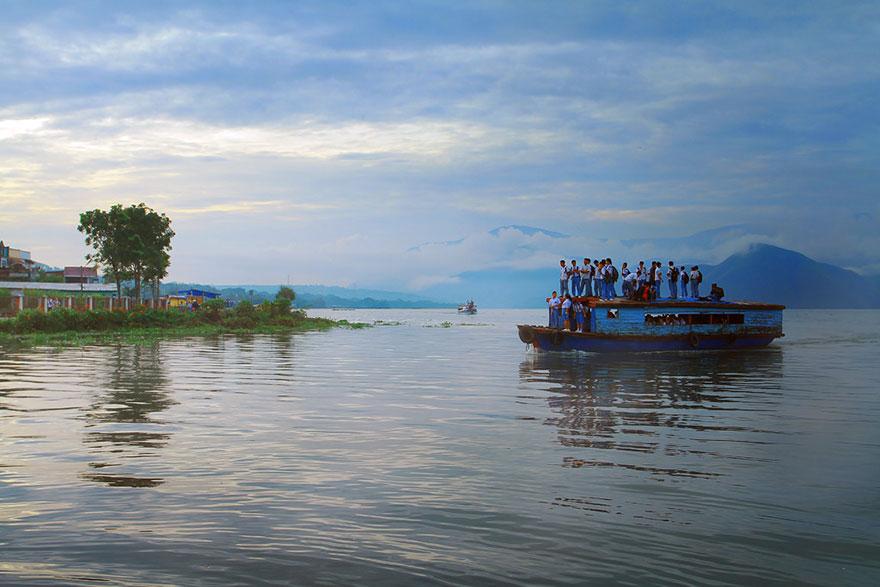 木製ボートの屋根に乗る子供たち。インドネシア