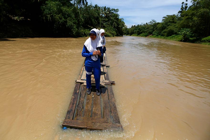ありもので作った船で川を渡る学生。インドネシア