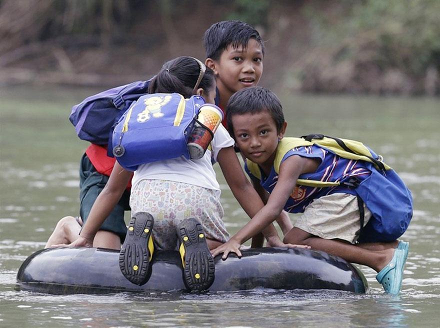 タイヤチューブを浮き輪代わりにして川を渡る小学生。フィリピン