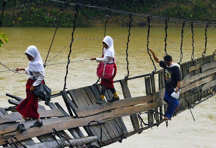 壊れたつり橋を渡る生徒。インドネシア