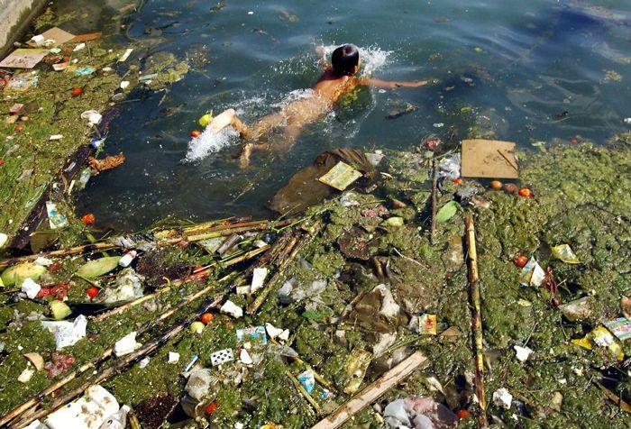 汚染された貯水池で泳ぐ子供