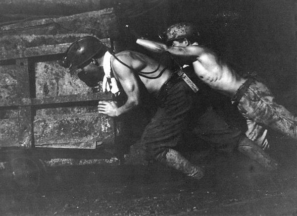 資材を積んだ台車を押す軍艦島の坑内員(長崎文献社提供)