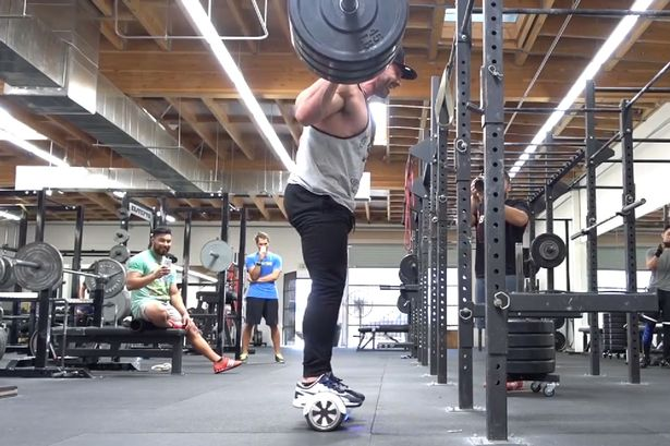 Man-squats-315-lbs-while-on-a-hoverboard-segway-2